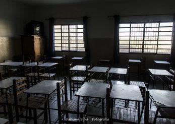 Na foto há uma sala de aula iluminada apenas pela luz das janelas e carteiras vazias. Foto: Fabiano Silva Fotografia